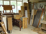 A workshop full of wooden products i.e. shelving, bench, bed frames, cabinets